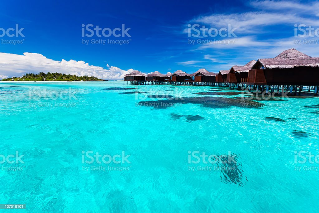 Overwater bungallows in blue lagoon stock photo