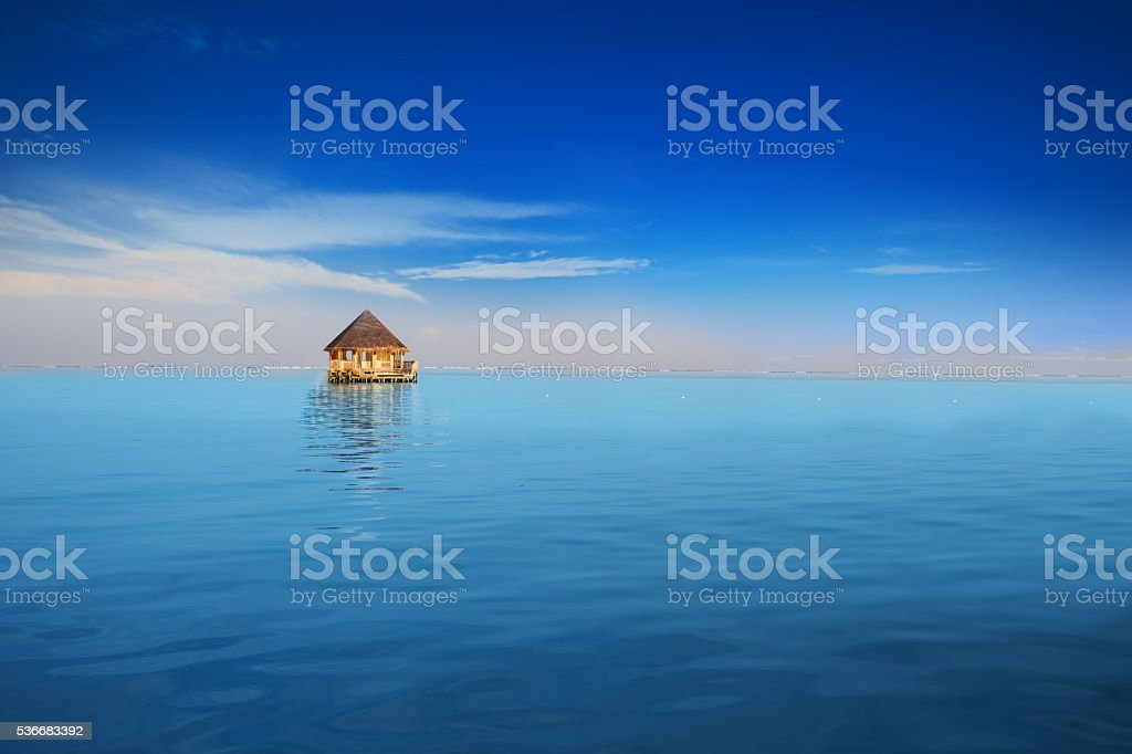 Overwater bungalow in blue tropical lagoon stock photo