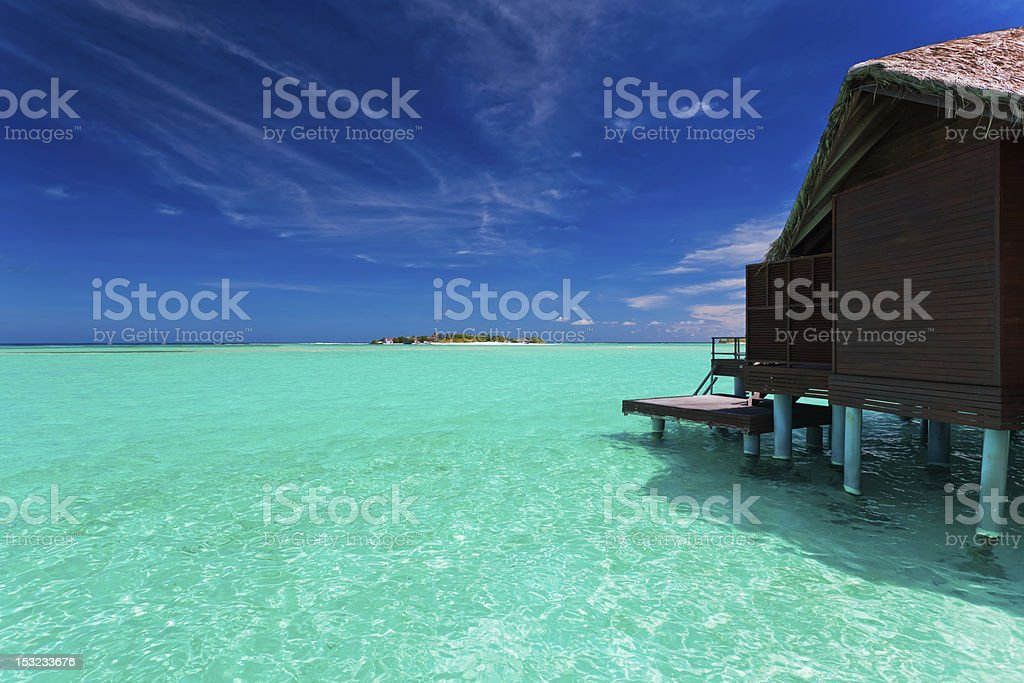 Overwater bungalow in lagoon around tropical island stock photo