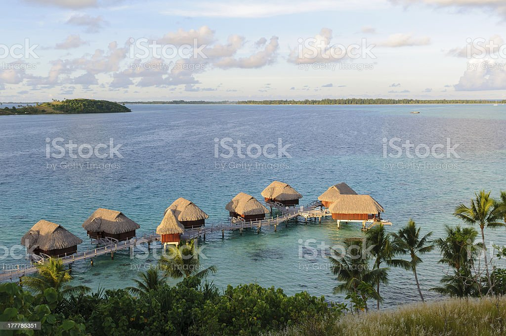 Overwater Bungalows in clear blue water stock photo