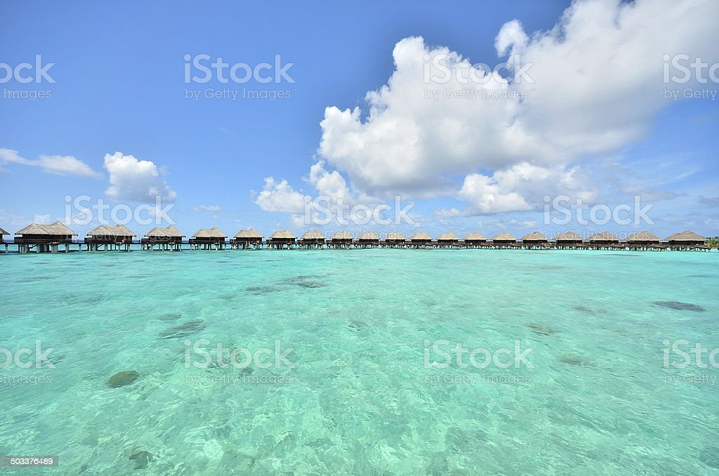 Overwater holiday villas on the tropical green lagoon stock photo