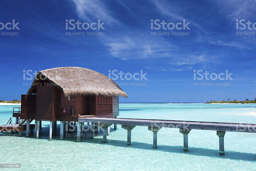 Overwater villas in blue lagoon of an island stock photo