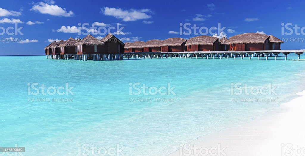 Overwater villas in blue tropical lagoon with white beach stock photo
