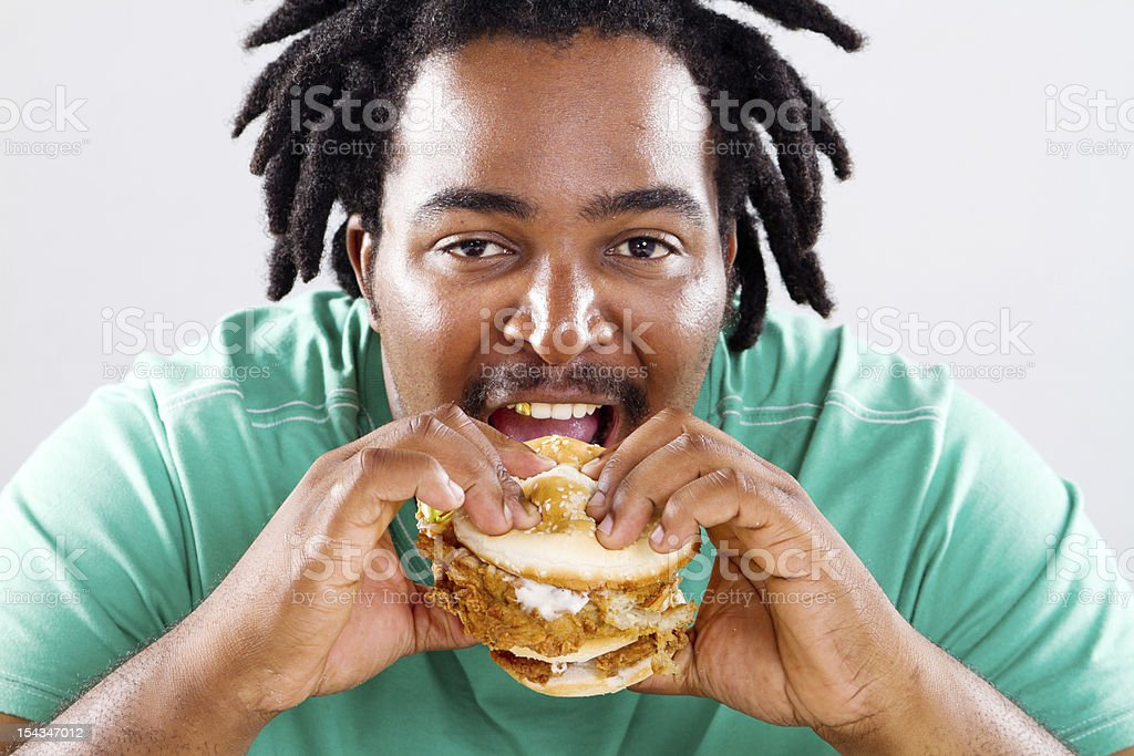 overweight african american man eating hamburger royalty-free stock photo