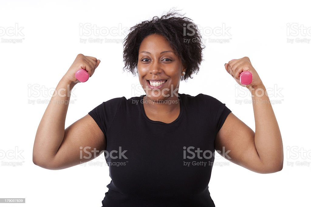 Overweight black woman working out with pink weights stock photo