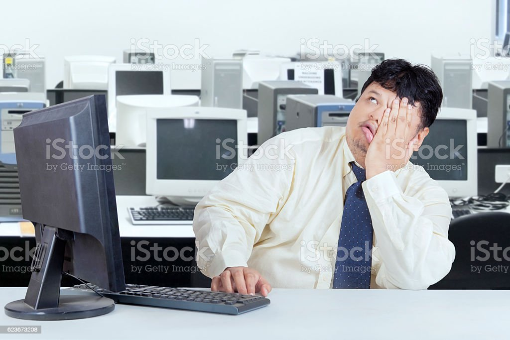 Overweight businessman alone in the office stock photo