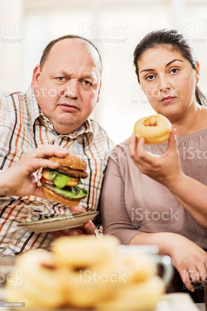 Overweight couple eating unhealthy food. stock photo