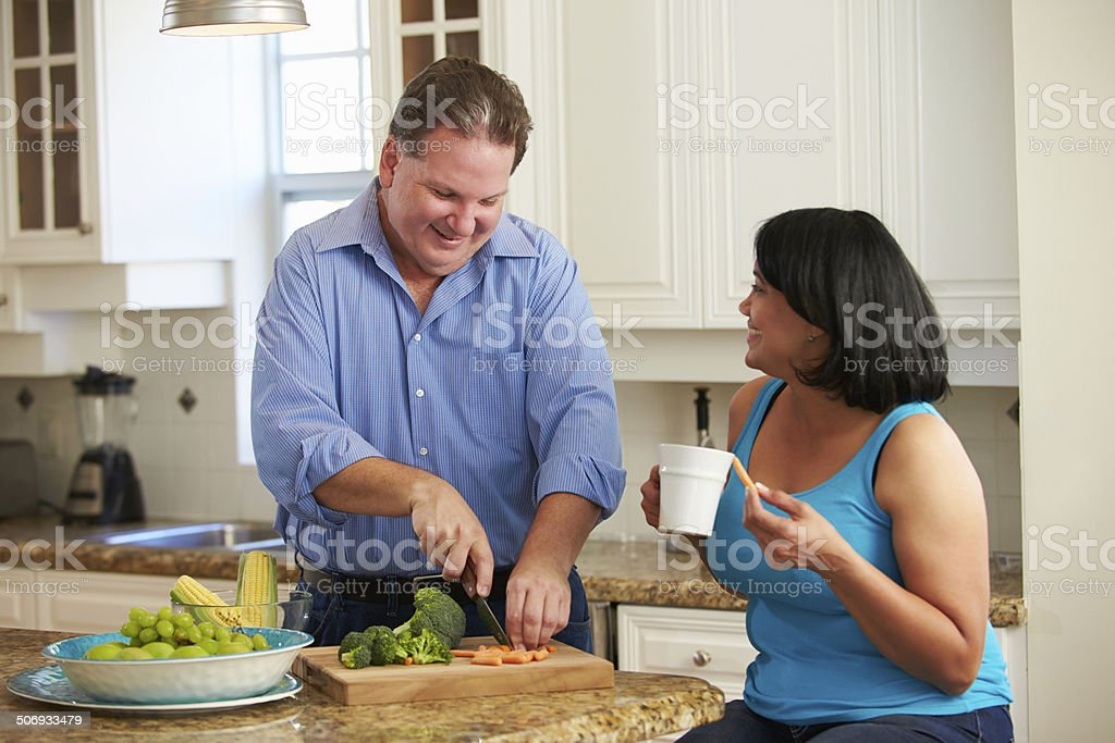 Overweight Couple On Diet Preparing Vegetables In Kitchen stock photo