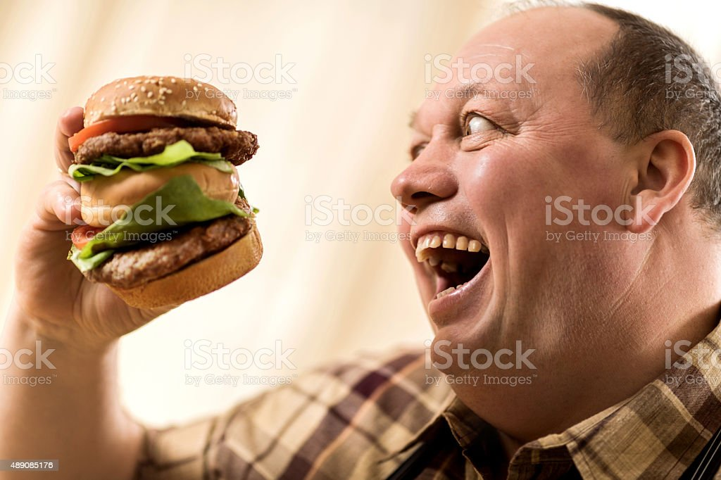 Overweight excited man about to eat a huge hamburger. stock photo