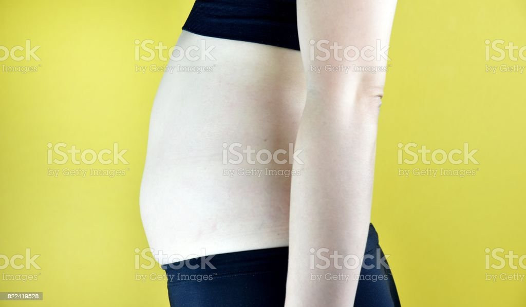 Overweight fat woman, Middle-aged woman with excessive belly fat, Side view of woman muffin top waistline. stock photo