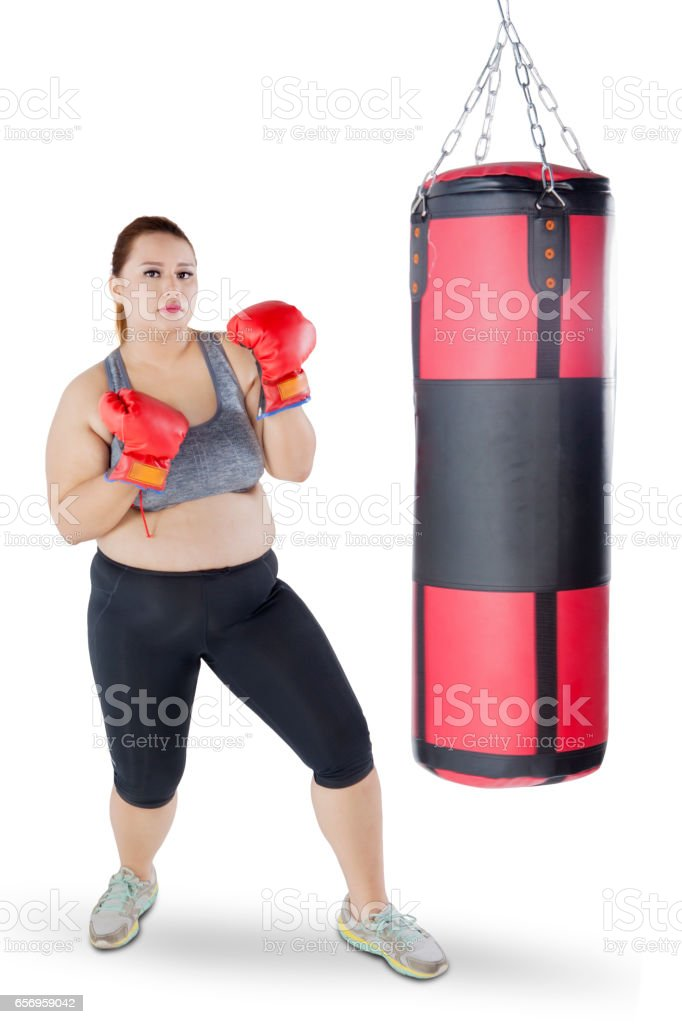 Overweight girl with boxing gloves and sack stock photo