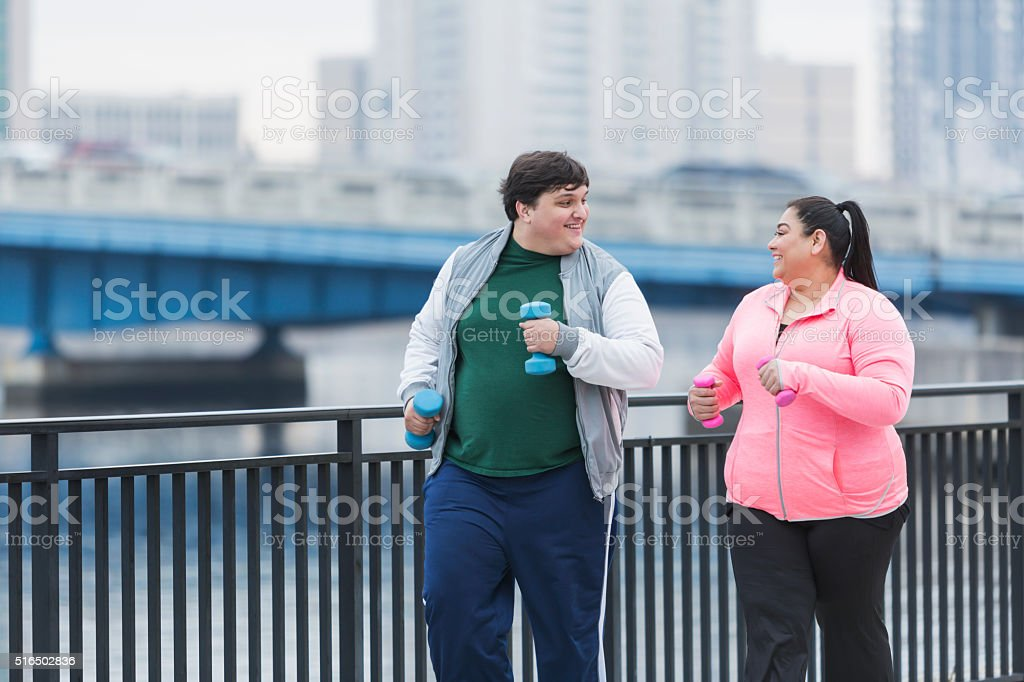 Overweight Hispanic man and woman exercising together stock photo