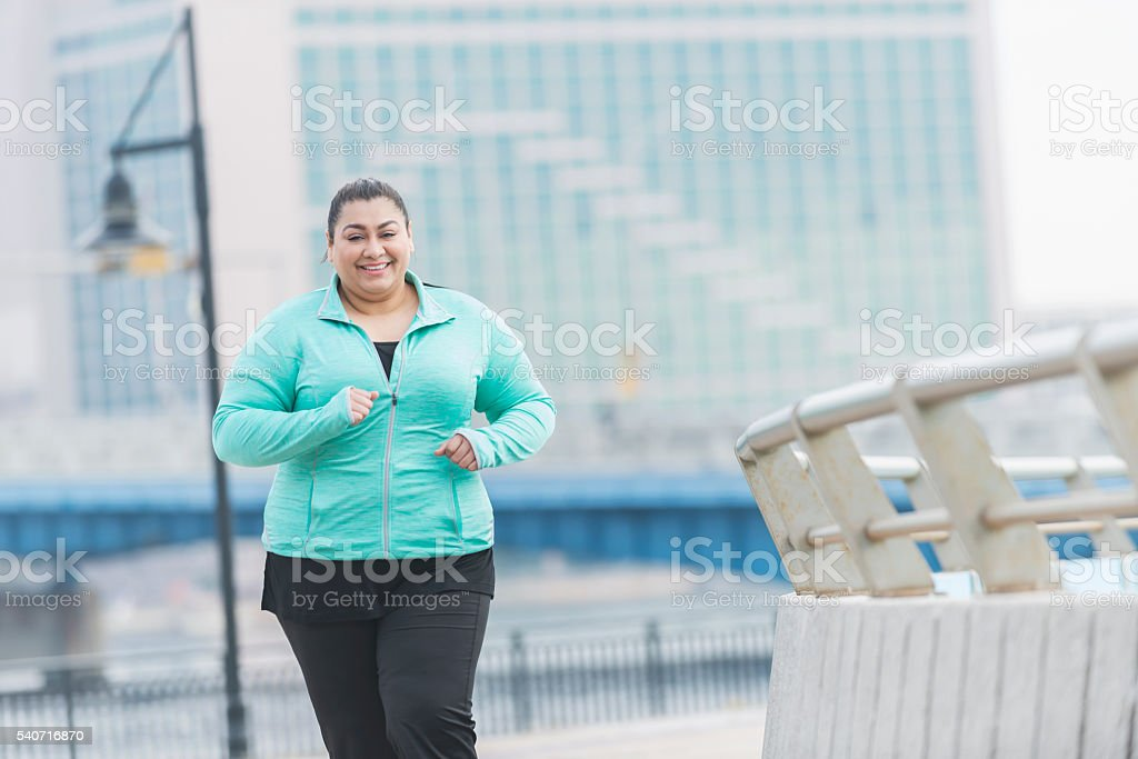 Overweight Hispanic woman running or jogging outdoors stock photo