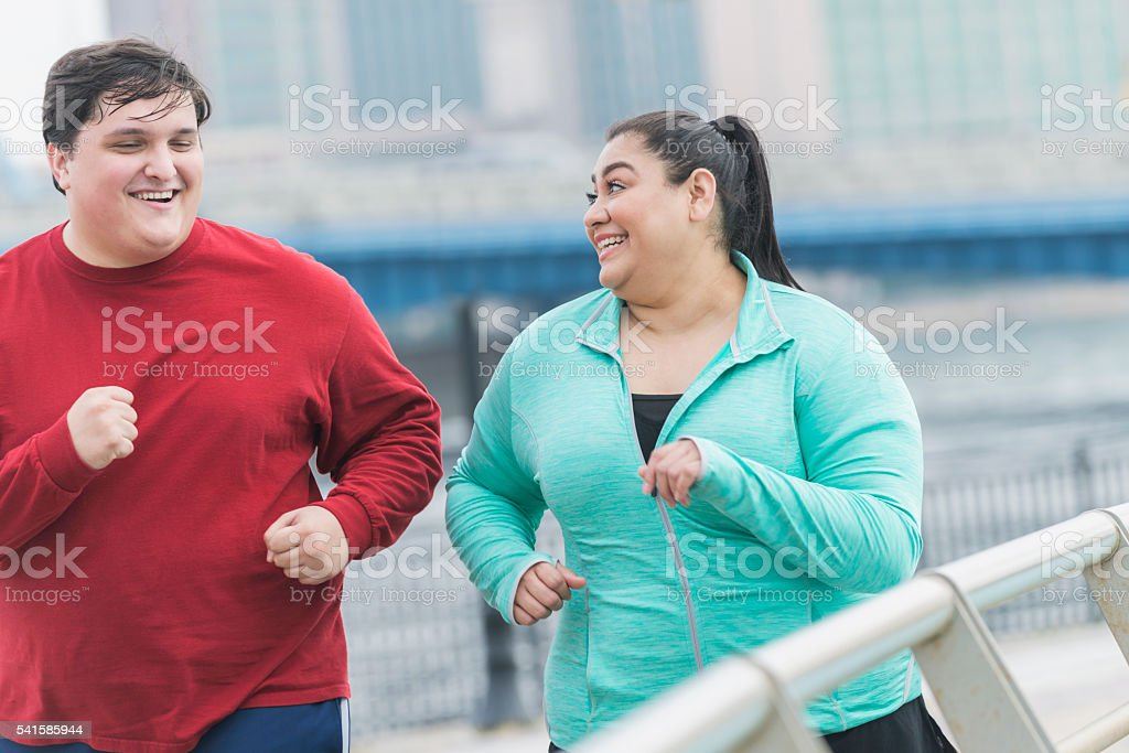 Overweight man and woman jogging in the city stock photo