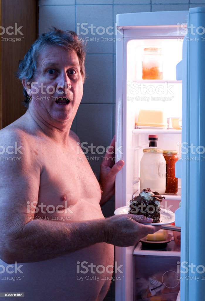 Overweight man caught at a fridge holding a piece of a cake royalty-free stock photo