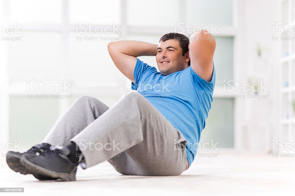 Overweight man exercising and doing sit-ups. stock photo