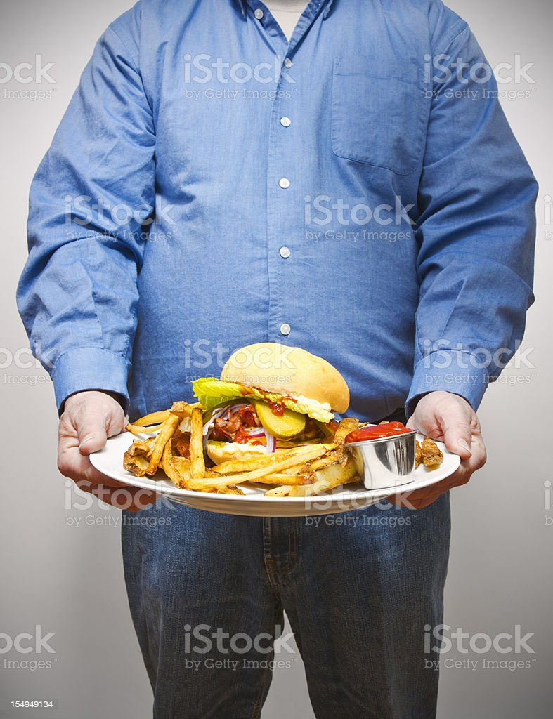 Overweight man holding a very large plate of fried food royalty-free stock photo