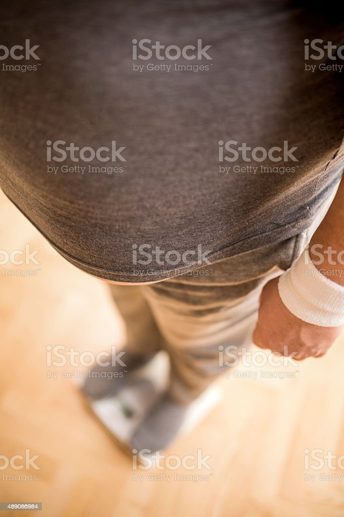 Overweight man on a weight scale. stock photo