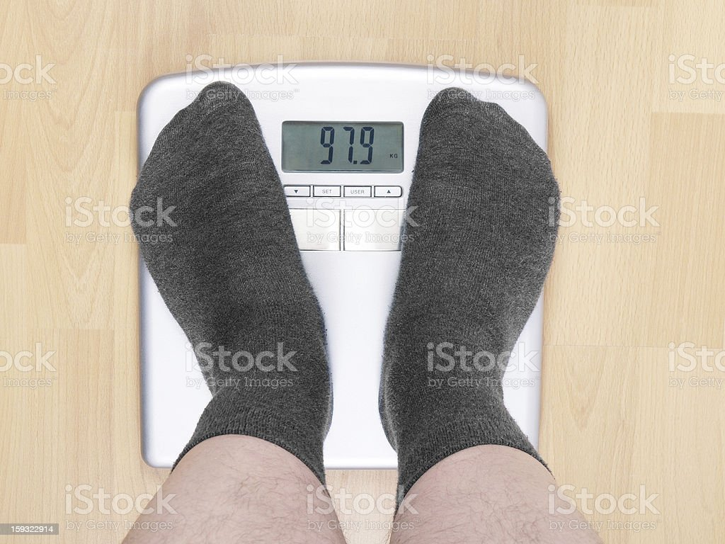 overweight man on scales stock photo