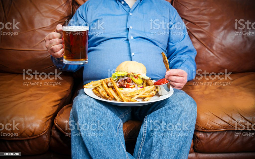 Overweight man over-eating on a couch stock photo