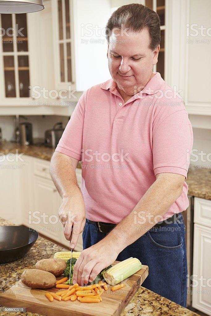 Overweight Man Preparing Vegetables in Kitchen stock photo