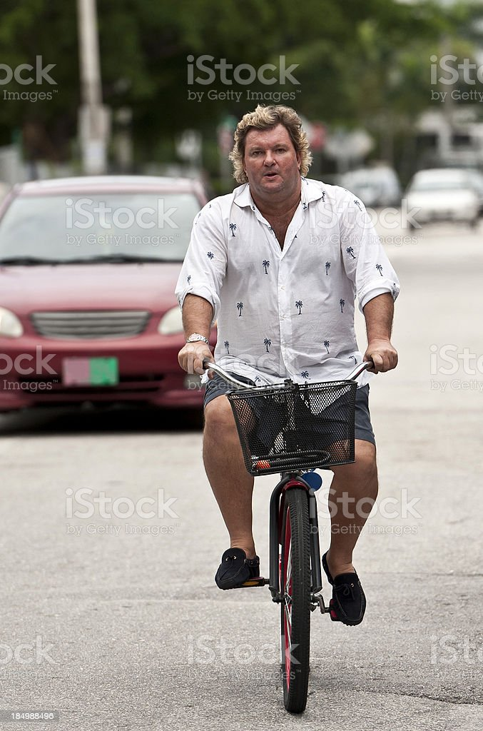 Overweight man raiding a bicycle royalty-free stock photo