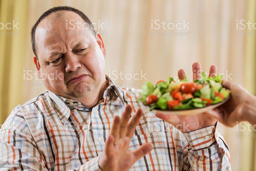 Overweight man refusing salad. stock photo