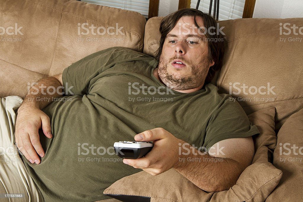 Overweight man watching TV on the couch stock photo