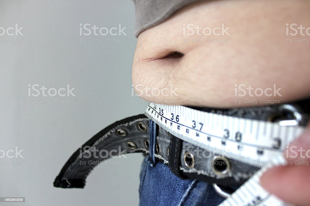 Overweight man with a fat tummy spilling over jeans, measuring stock photo