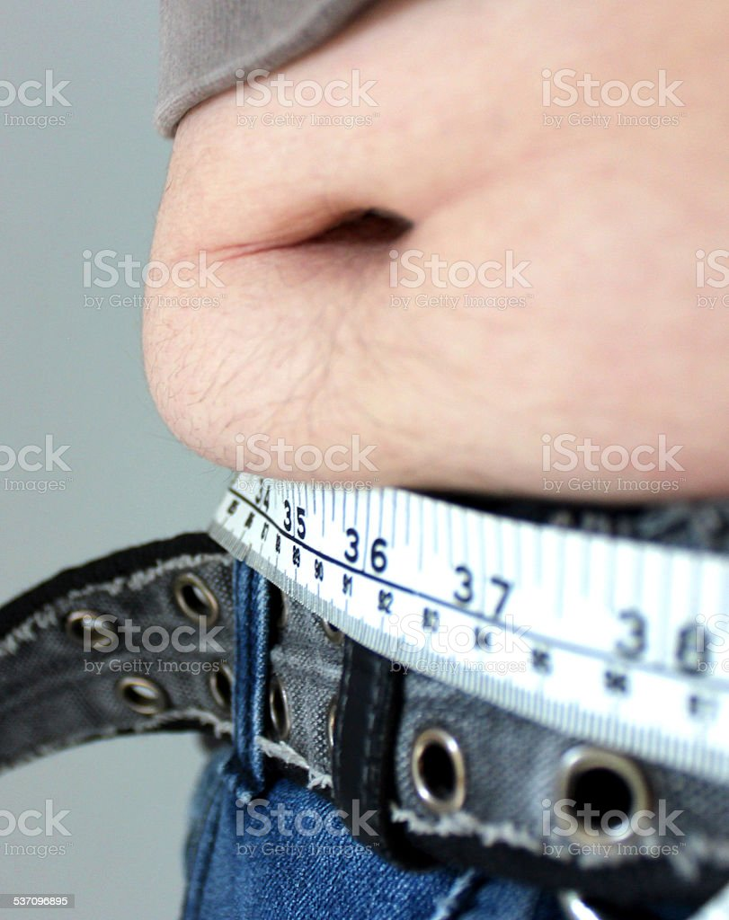 Overweight man with a fat tummy spilling over jeans, measuring-tape stock photo