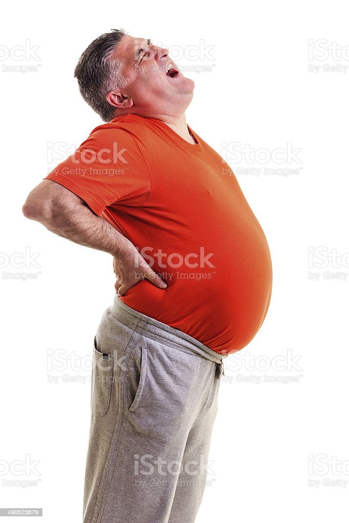 Overweight man with acute back ache bending over backwards stock photo