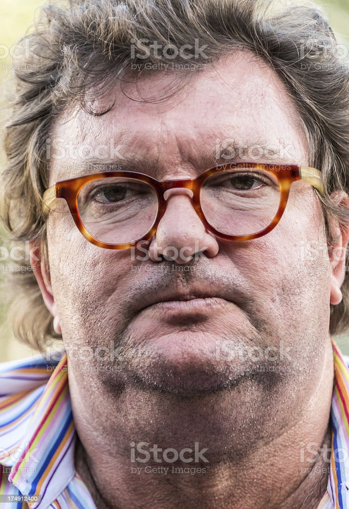Overweight man with glasses facial hair, and a serious face royalty-free stock photo