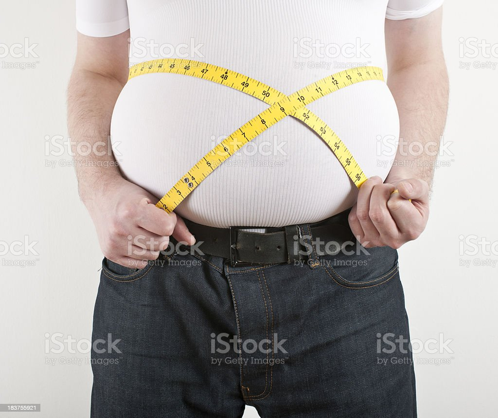 Overweight man with tape measure around belly stock photo