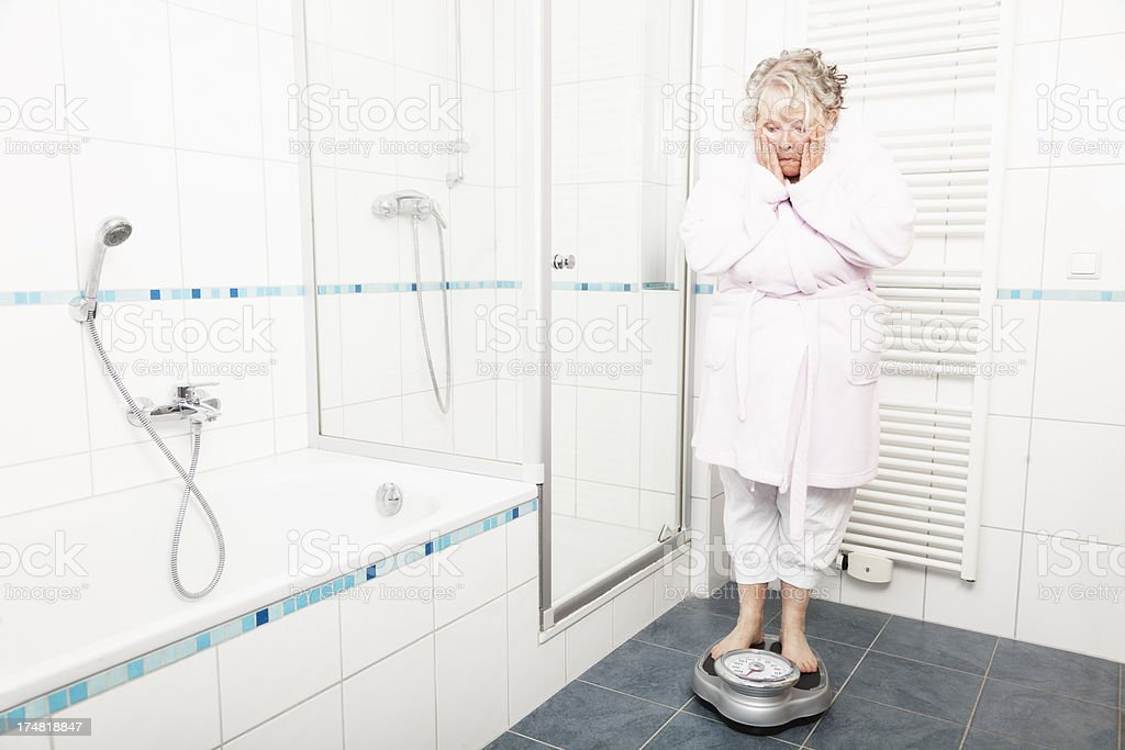 overweight mature woman bathroom scale royalty-free stock photo
