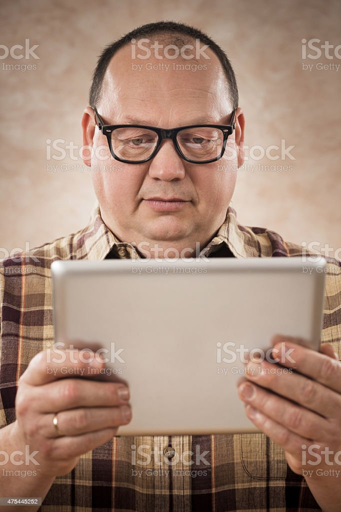 Overweight nerdy man using digital tablet. stock photo