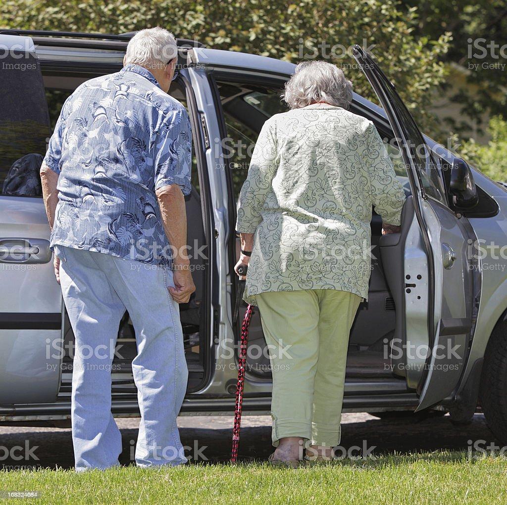 Overweight Senior Couple Getting Into Minivan Car stock photo