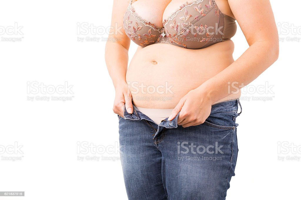 Overweight woman can't close her jeans stock photo