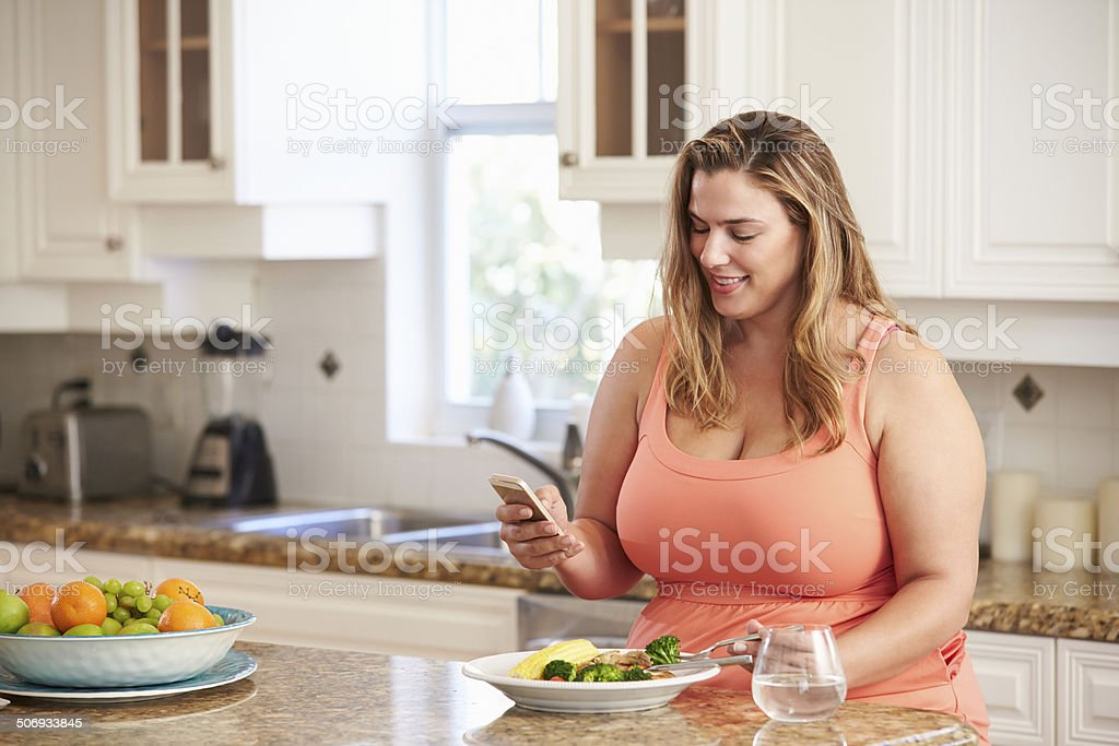 Overweight Woman Eating Healthy Meal And Using Mobile Phone stock photo