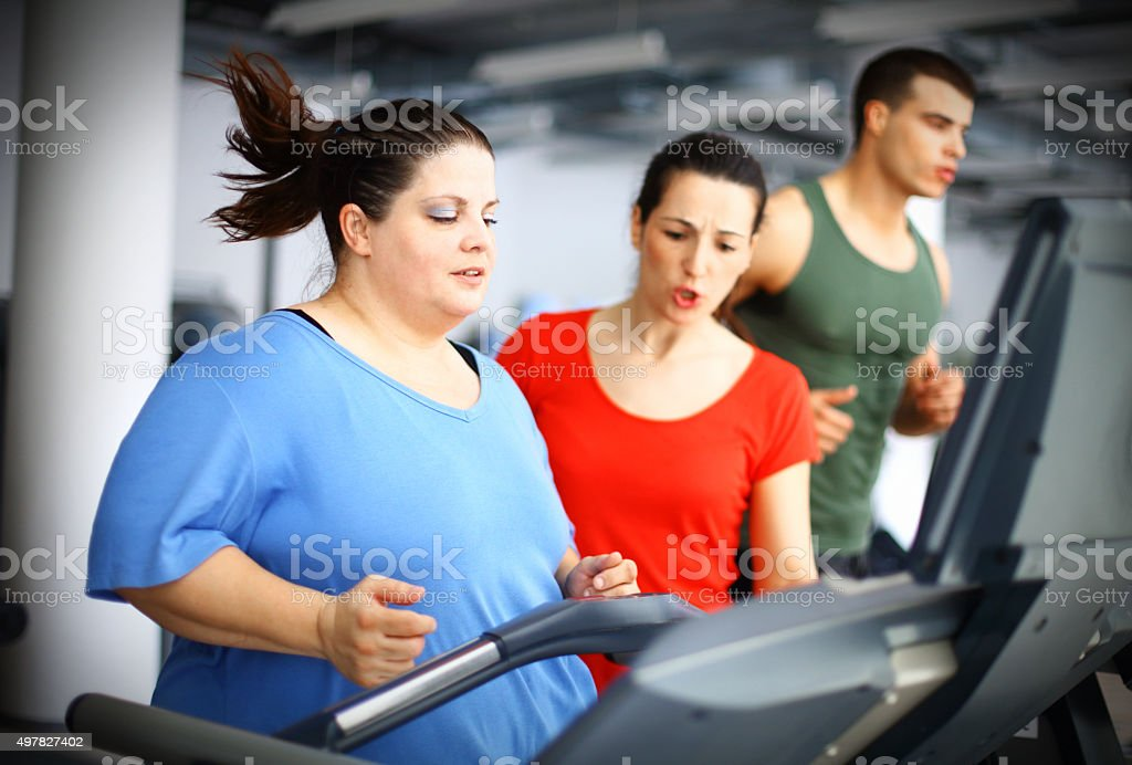 Overweight woman exercising on a treadmill. stock photo