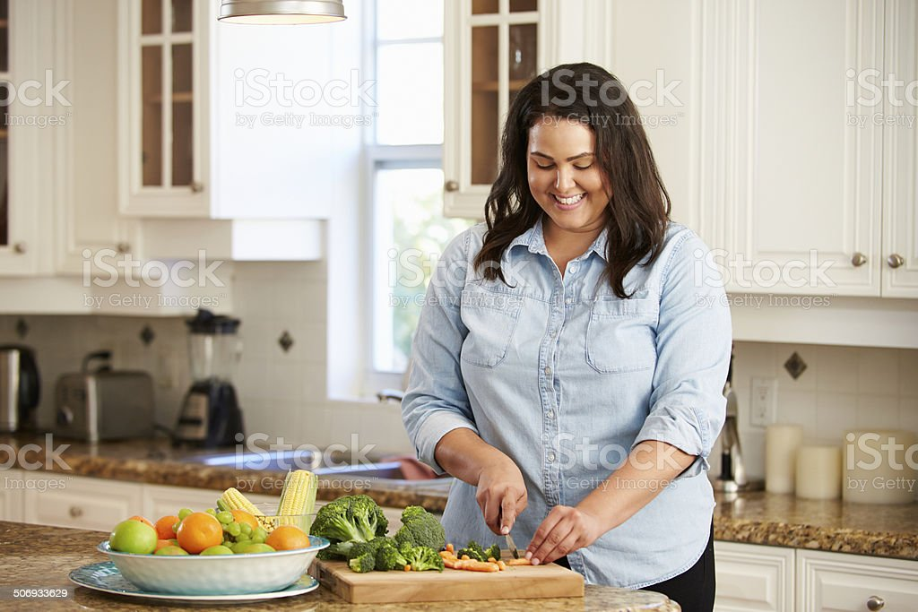 Overweight Woman Preparing Vegetables in Kitchen stock photo