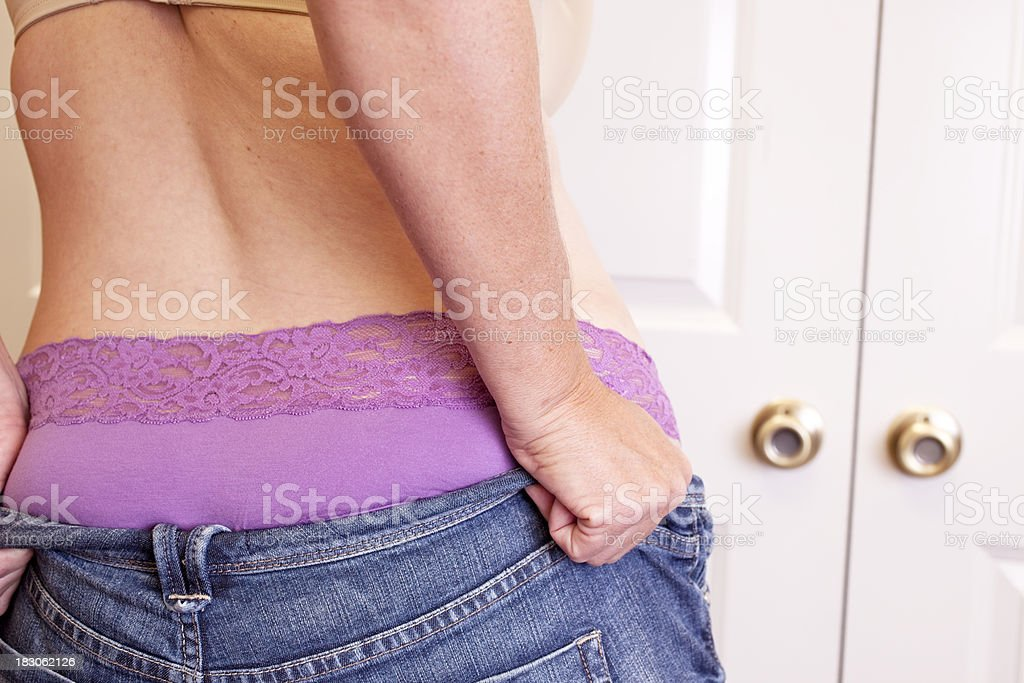 Overweight woman pulling on her tight jeans. stock photo