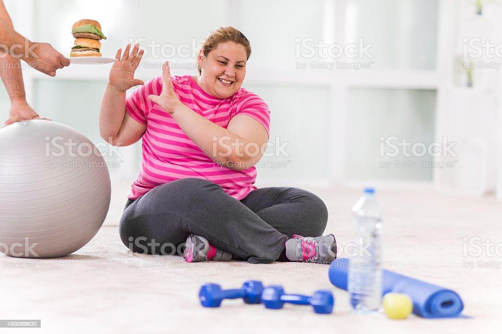 Overweight woman refusing hamburger. stock photo