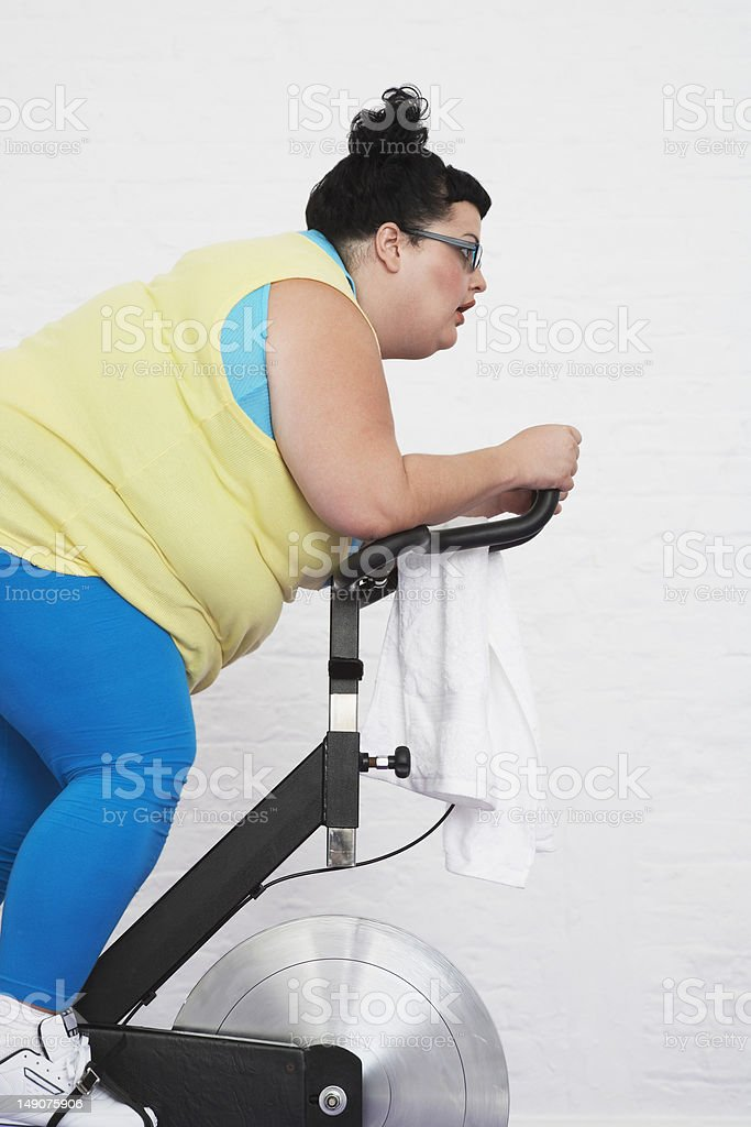 Overweight Woman Riding Exercise Bike stock photo