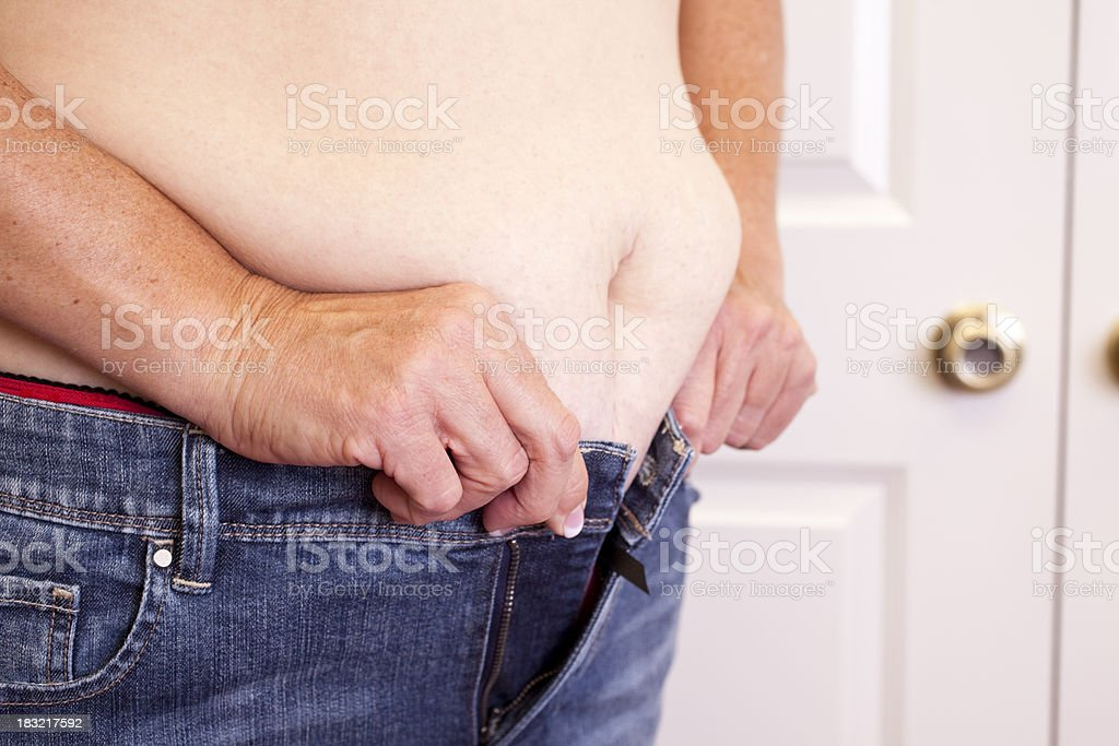 Overweight woman trying to button her tight jeans. stock photo