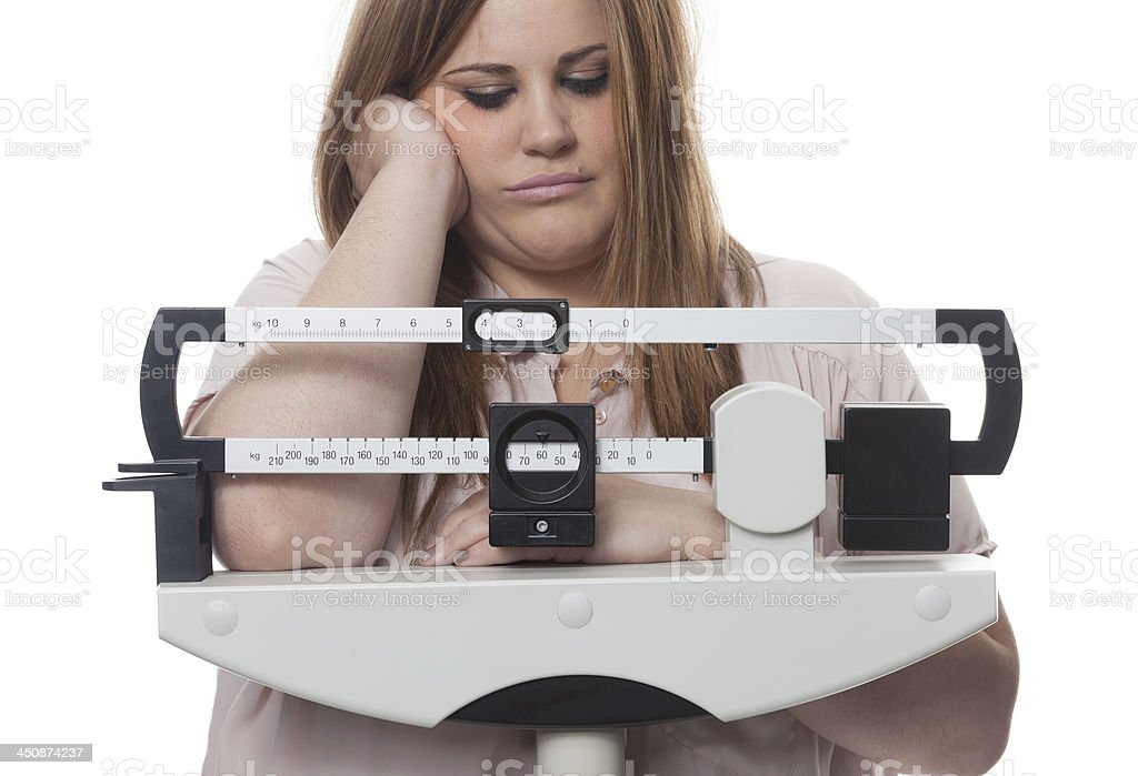 Overweight woman with depressed expression looking at scale stock photo