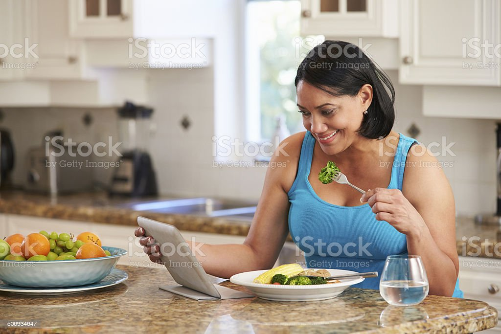 Overweight Woman With Digital Tablet Checking Calorie Intake stock photo