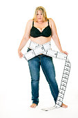 Overweight woman with tape measure around waist.