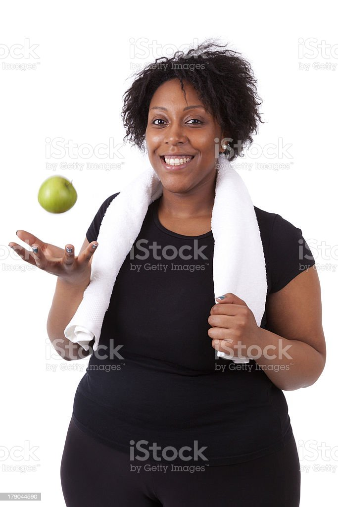 Overweight young black woman holding an apple - African people stock photo