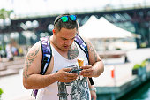 Overweight young male with ice creame checking his smart phone