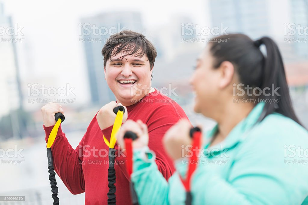 Overweight young man, friend exercising together stock photo